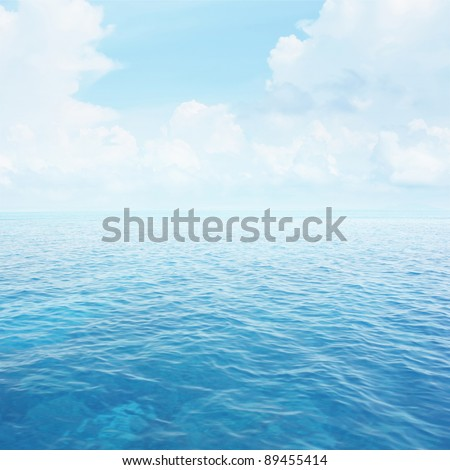 Blue clear sea with waves and sky with fluffy clouds