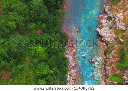Blue clear water flowing at the bottom of a canyon - stock photo