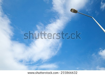 Blue cloudy sky and modern street lamp - stock photo