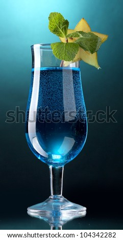 Blue cocktail in glass on blue background - stock photo