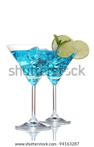 Blue cocktail in martini glasses with ice isolated on white