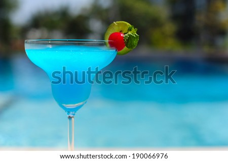 Blue cocktail on swimming pool side - stock photo