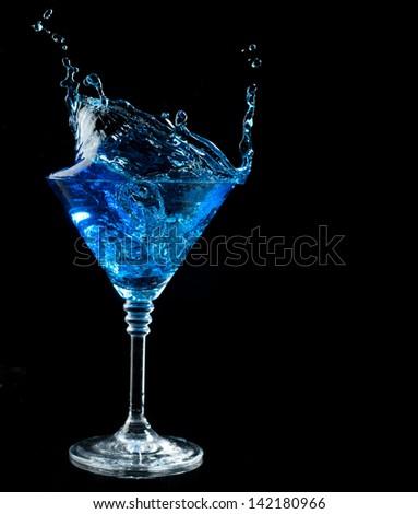 blue cocktail splashing into glass on black background - stock photo