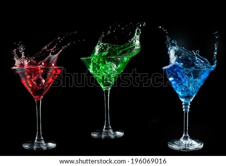 blue cocktail splashing into glass on black background - stock photo