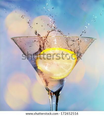 Blue cocktail with liquid splashing - stock photo
