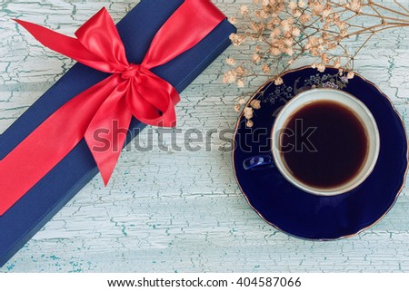 Blue coffee cup, gift box and small flowers on wooden table, rustic style - stock photo