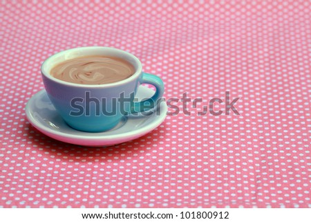Blue coffee cup on pastel pink plaid fabric table - stock photo