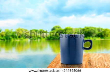 Blue Coffee cup on wood table at blur tree and lagoon background - stock photo
