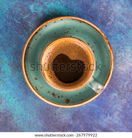 Blue coffee cup with heart shape made of foam on blue wooden background. Square image - stock photo