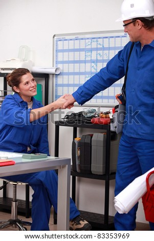 blue collar coworkers shaking hands