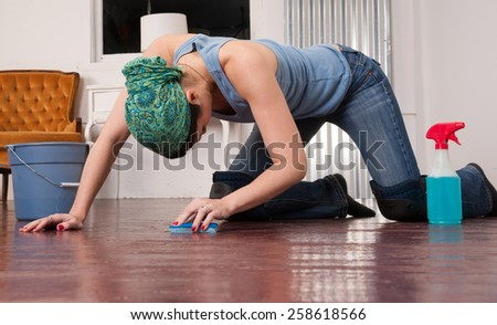 Blue Collar Worker Maid Doing Cleaning Chores Scrubbing Floor - stock photo