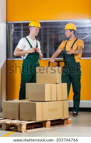 Blue-collar worker pushing fork pallet truck and talking with his collaborator - stock photo