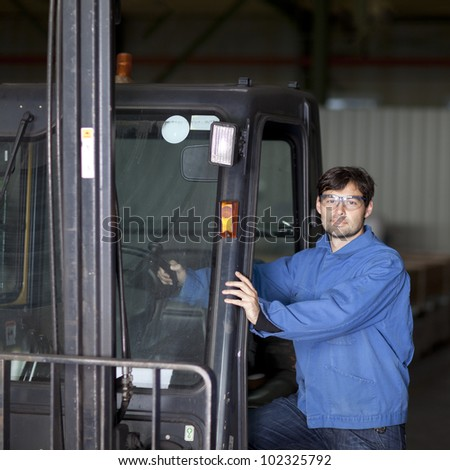 Blue collar worker with fork lift truck - stock photo
