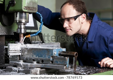 Blue-collar worker with safety glasses at milling machine in workshop. - stock photo