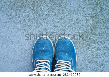 blue color, dirty hiking boots on a concrete, rough background with lots of copy space, top view, horizontal - stock photo