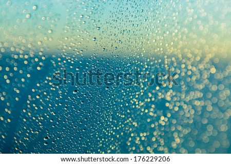 Blue color of ocean behind rain or spray drops on window of cruise ship as the sun starts to rise at dawn and illuminate the water - stock photo