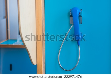 Blue color telephone on blue wall. - stock photo