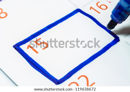 Blue color writing on the calendar at 15. - stock photo
