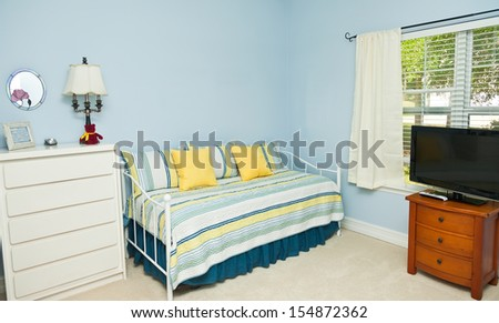 Blue colored walls in a bedroom with a daybed, TV, and dresser - stock photo