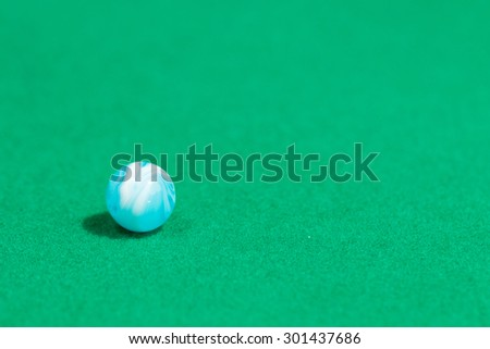 Blue Colorful Marble Ball on Green background - stock photo