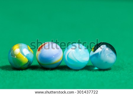 Blue Colorful Marble Balls on Green background - stock photo