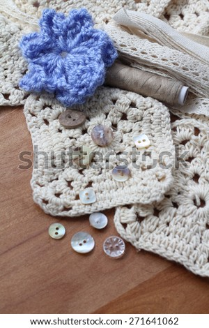 Blue crochet flower  with cream square pattern crochet squares , on a dark wood table, showing different crochet style and yarns, and vintage cream pretty buttons, lace bundle and beige sewing thread - stock photo