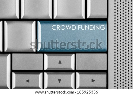 Blue CROWD FUNDING key on a computer keyboard with clipping path around the CROWD FUNDING key - stock photo