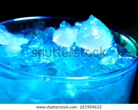 Blue cube ice of cold drink  on dark background. Top view. Close up.