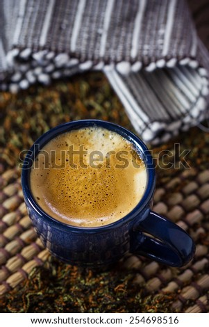 Blue cup of espresso coffee on plate mat - stock photo
