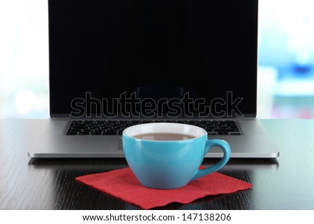 Blue cup on napkin on laptop background on wooden table - stock photo