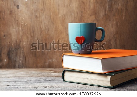blue cup with red heart on green and orange books on grunge wooden table - stock photo