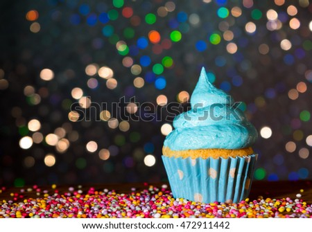 Blue cupcake with swirl frosting and sprinkles with a bokeh background
