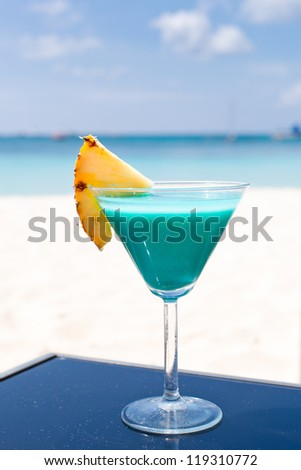 Blue Curacao cocktail with slice of pineapple on white beach - stock photo