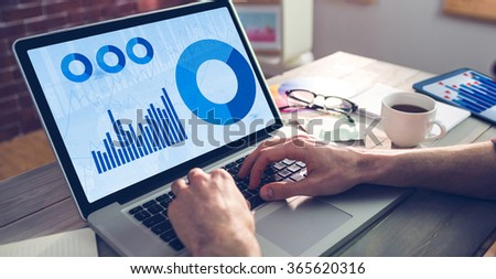 Blue data against cropped hand of graphic designer using laptop - stock photo