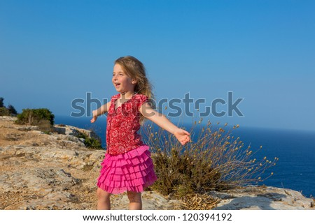 blue day with kid girl open hands to the wind and Mediterranean sea - stock photo