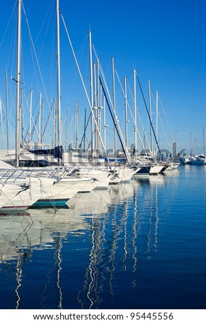 Blue Denia marina port in Alicante Spain with boats in a row - stock photo