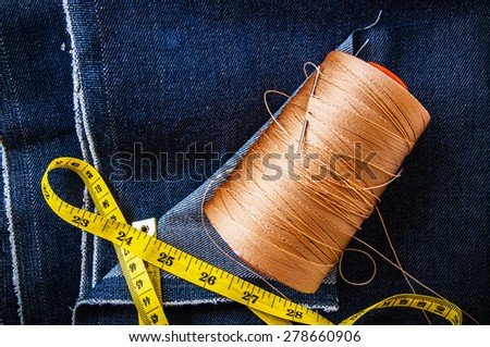 Blue Denim Jean Fabric with Measure Tape,Threads Reel,Needle for Embroidery / Concept and Idea of Denim Industry, Sewing and Fashion, Vintage Rustic Style. Pattern, Background, Wallpaper and Textured. - stock photo