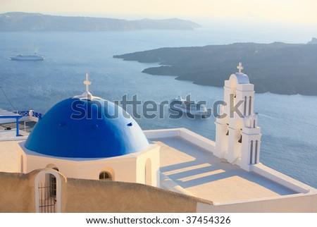 Blue domed church in Imerovigli overlooks spectacular caldera surrounding beautiful island of Santorini, Greece - stock photo