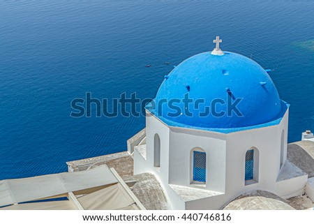Blue domed church in Oia village on top of the cliffs on Santorini in the Greece Islands - stock photo