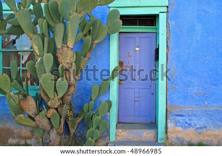 blue door in green frame, vintage Spanish adobe building - stock photo