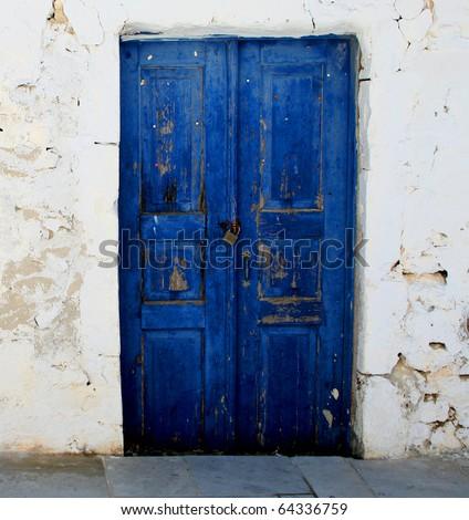 blue door set in a rock wall - stock photo