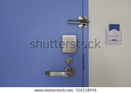 blue door with stainless steel handle lock set and access control card in socket on wall - stock photo