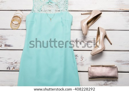 Blue dress and golden bag. Lace insert dress on table. Lady's silver handbag with shoes. Seasonal sale of stylish clothing. - stock photo