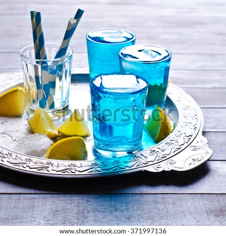 Blue drink with ice in a glass on a wooden background. Selective focus. - stock photo