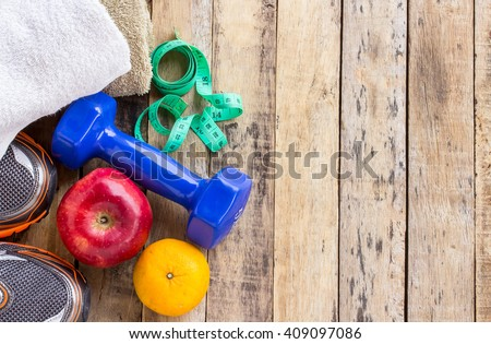 Blue dumbbell, white towel, measuring tape and red apple on wooden table. Fitness concept - stock photo