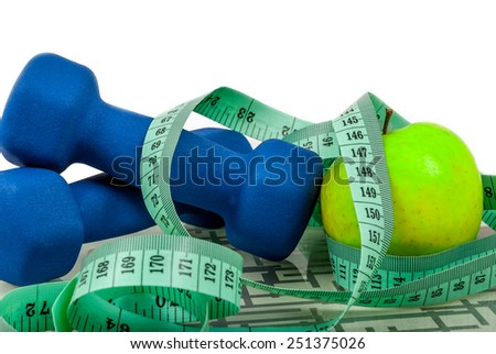 Blue dumbbells and apple and measure tape on weighing machine - stock photo