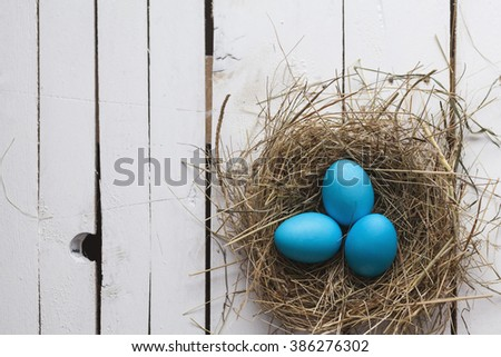 Blue Easter eggs in nest on wooden background - stock photo
