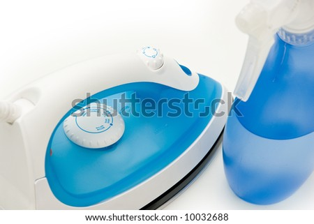 Blue electric iron isolated on white and a spray bottle
