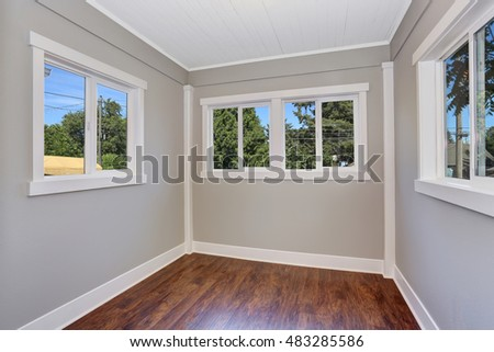 Blue empty room interior with hardwood floor and many windows. Northwest, USA