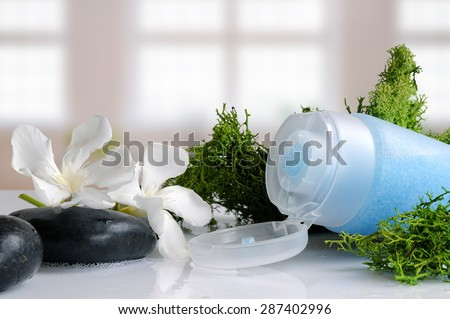 Blue exfoliating gel with seaweed on a white glass table in a bath - stock photo